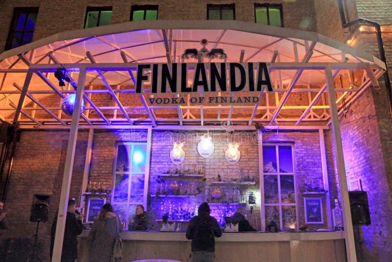 Oidentifierat folk i Finlandia vodkastång på den utomhus- gatan Foo royaltyfri fotografi