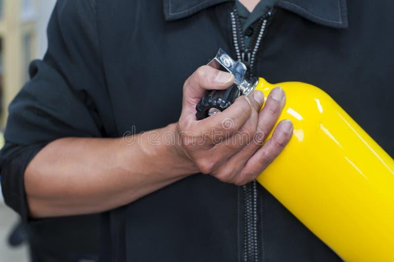 Oidentifierat folk som rymmer den gula syrebehållaren Mannen förbereder sig och arkivbild