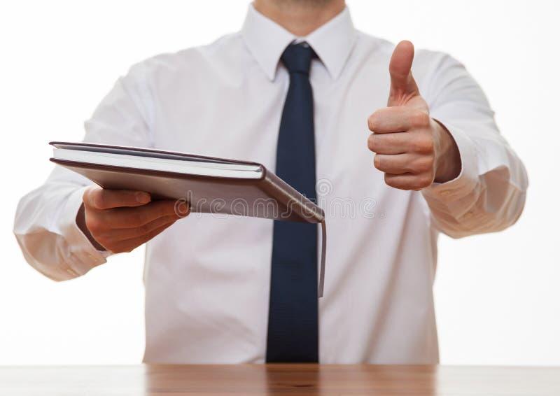 Oigenkännlig affärsman som ger en bok och visar upp en tumme royaltyfri bild