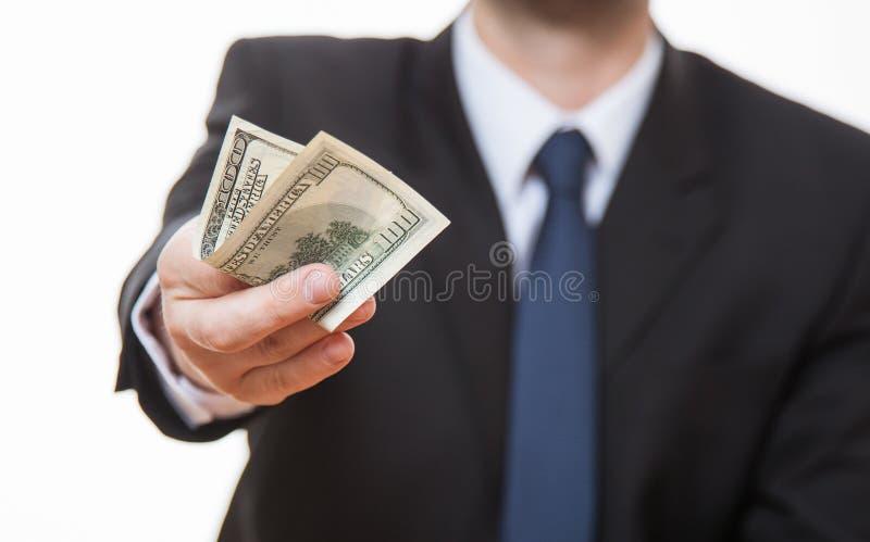 Oigenkännlig affärsman som ger hundra dollar arkivbild