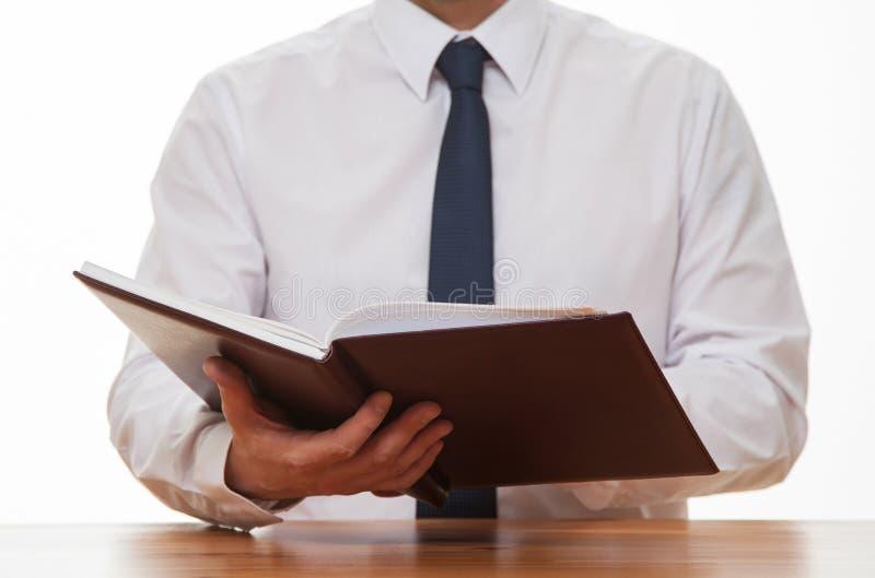Oigenkännlig affärsman som läser en bok arkivbilder
