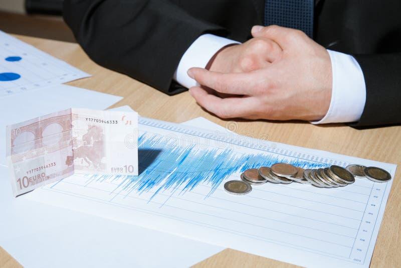 Oigenkännlig affärsman som räknar euromynt arkivfoton