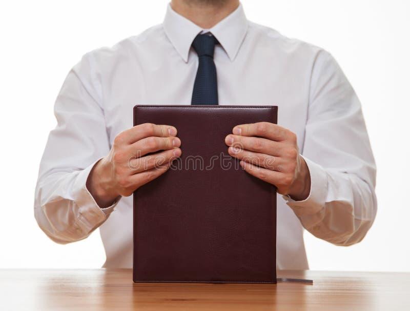 Oigenkännlig affärsman som rymmer en bok arkivfoto