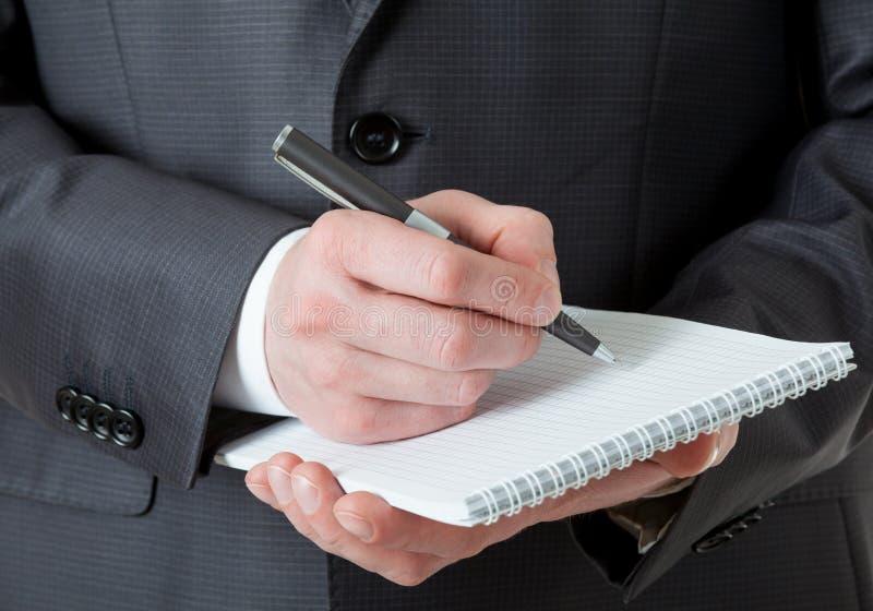 Oigenkännlig affärsman som rymmer en tom anteckningsbok och en penna royaltyfri foto