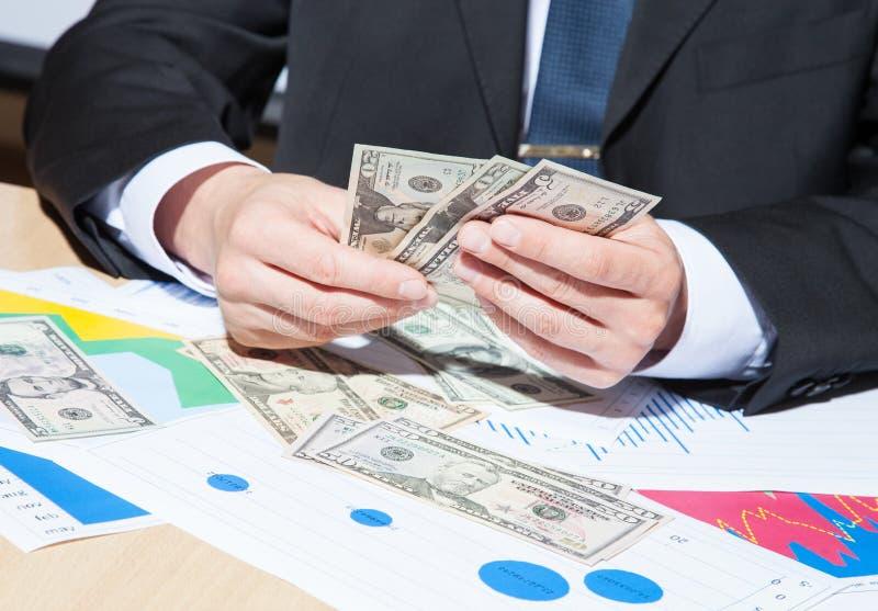 Oigenkännlig affärsman som rymmer pappers- pengar royaltyfri bild