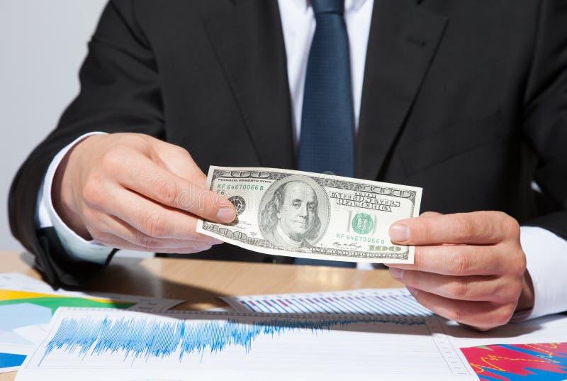 Oigenkännlig affärsman som rymmer pappers- pengar/dollar royaltyfria foton