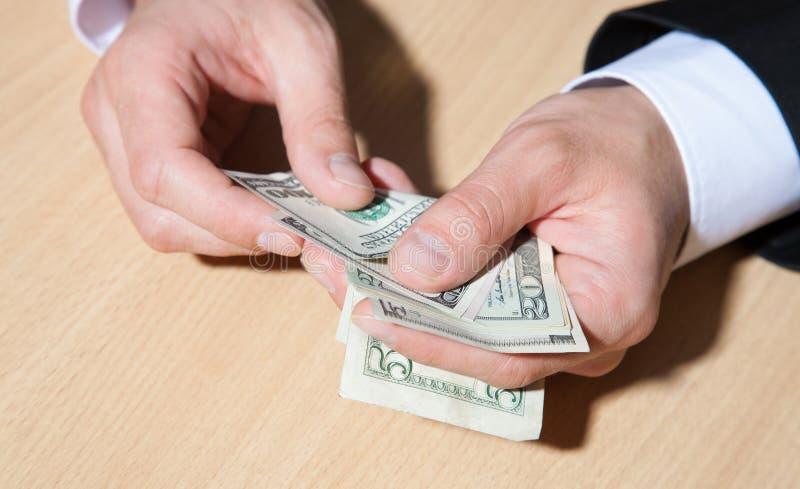 Oigenkännlig affärsman som rymmer pappers- pengar/dollar arkivbild