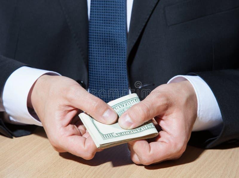 Oigenkännlig affärsman som rymmer pappers- pengar/dollar royaltyfri bild