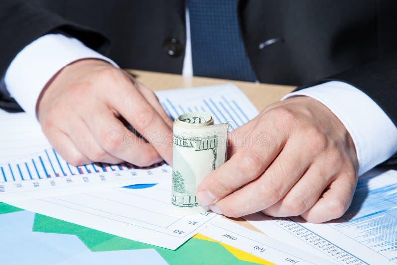 Oigenkännlig affärsman som rymmer pappers- pengar/dollar arkivfoton