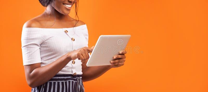 Oigenkännlig afrostflicka som använder Tablet över Orange-bakgrund, beskuren, Panorama royaltyfria foton