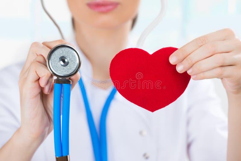 Oigenkännlig doktor med stetoskopet som rymmer röd mänsklig hjärta arkivbilder