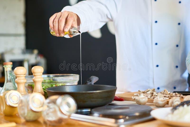 Oigenkännlig kock Frying Mushrooms royaltyfri fotografi