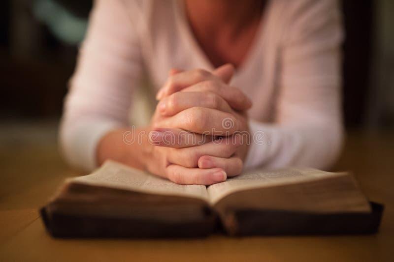 Oigenkännlig kvinna som ber, händer som tillsammans knäppas fast på hennes Bibl royaltyfri bild