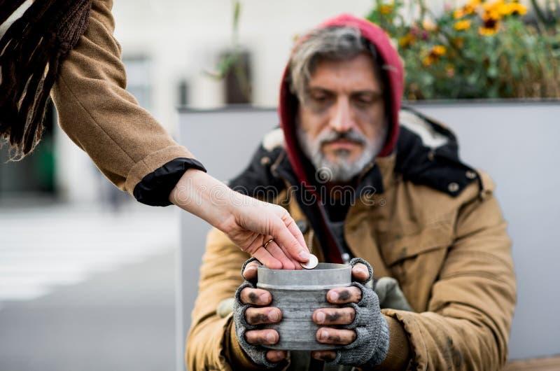 Oigenkännlig kvinna som ger pengar till den hemlösa tiggaremannen som sitter i stad royaltyfria foton
