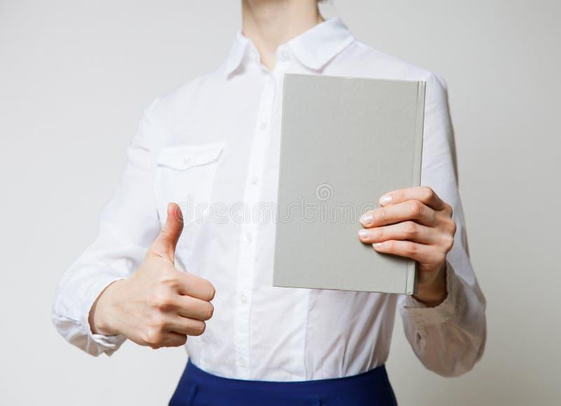Oigenkännlig kvinna som rymmer en bok fotografering för bildbyråer