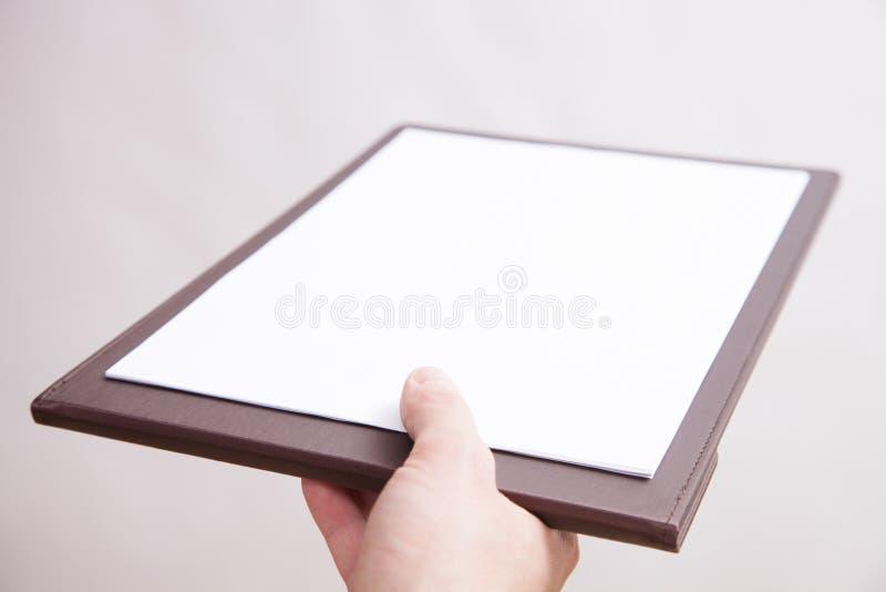 Oigenkännlig man som ger en skrivplatta royaltyfria foton