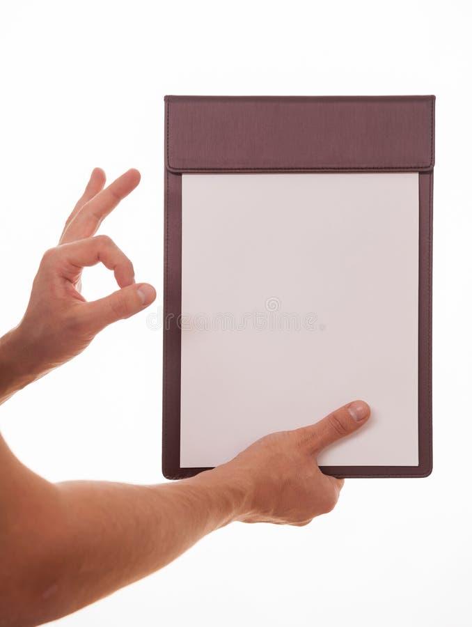Oigenkännlig man som rymmer en skrivplatta och visar ett tecken arkivbild