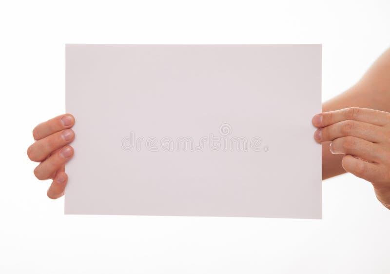 Oigenkännlig man som rymmer ett tomt ark av papper arkivbilder
