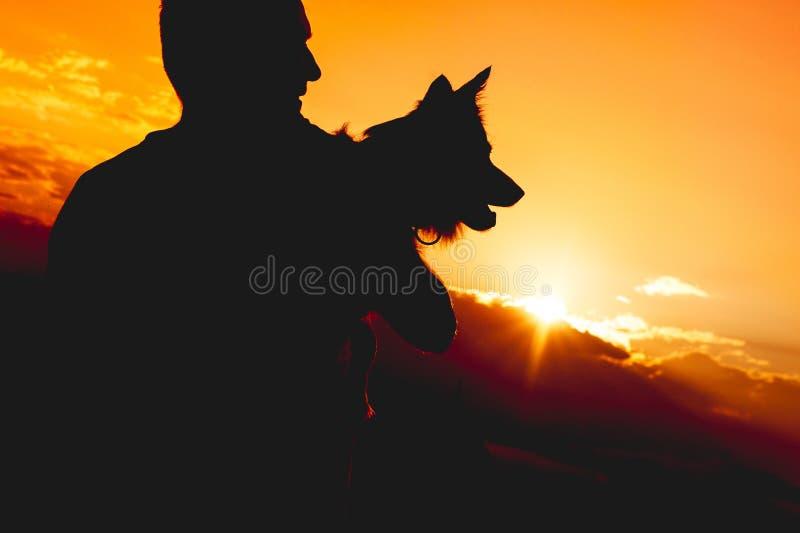 Oigenkännlig person som rymmer en hund Kontur mot solnedgång royaltyfri bild