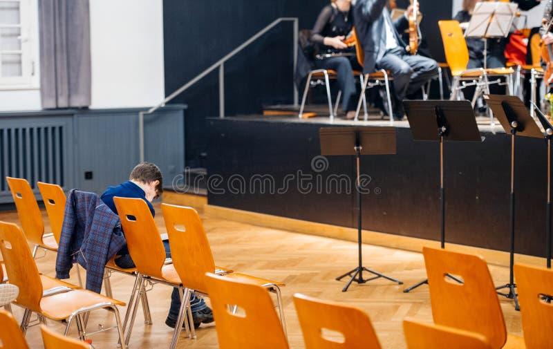 Oigenkännlig pojke som witing för att orkester ska börja deras lek arkivbilder