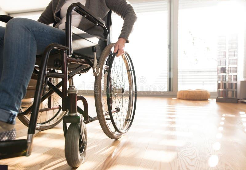 Oigenkännlig rörelsehindrad hög kvinna i rullstol hemma arkivbilder