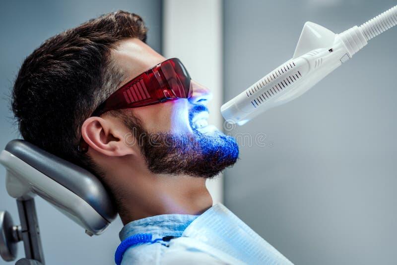 Oigenkännlig tandläkare som gör vit tänder av den unga mannen som sitter i tand- stol i modern klinik Slapp fokus royaltyfri foto