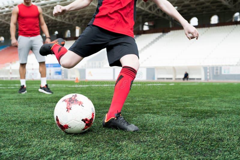 Oigenkännlig tonårs- pojke som sparkar bollen arkivfoton