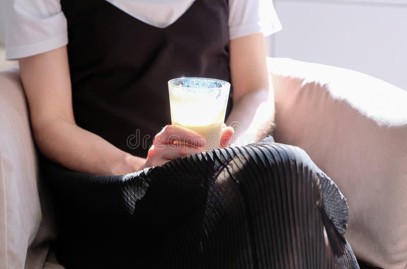 Oigenkännlig ung kvinna som rymmer en kopp kaffe arkivfoto