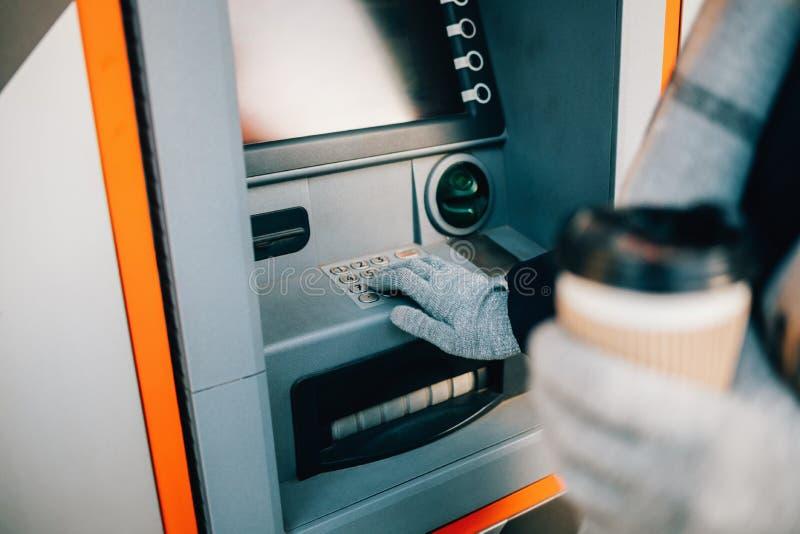 Oigenkännlig ung kvinna som trycker på knappar på ATM arkivfoton