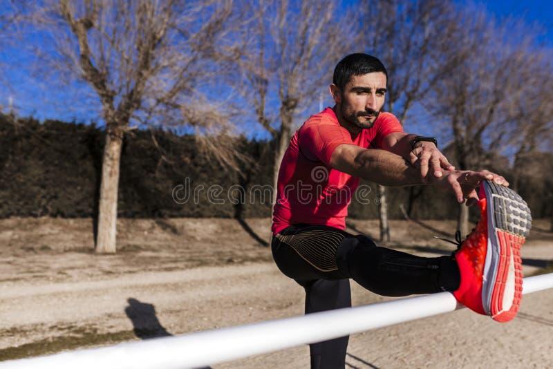 Oigenkännlig ung löparemanidrottsman nen som sträcker på loppspåret Sportar utomhus arkivfoto