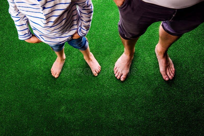 Oigenkännligt fader- och sonanseende, mot konstgjord gräsplan arkivfoto