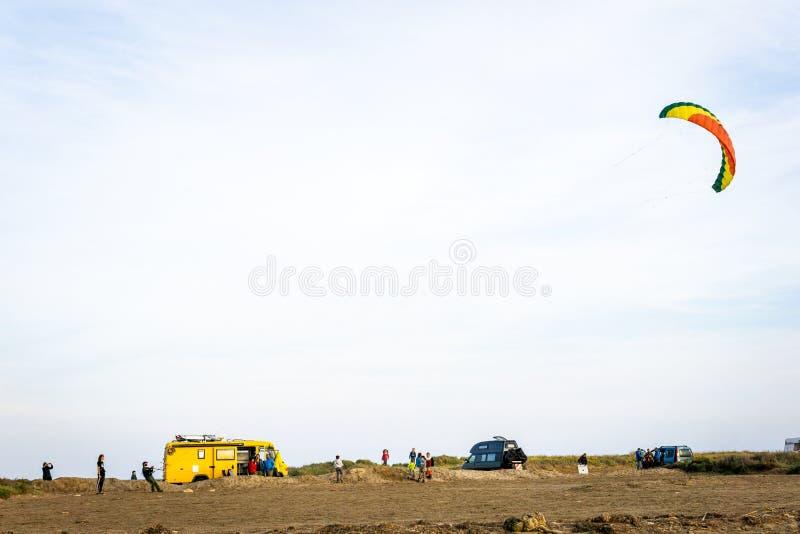 Oigenkännligt folk som flyger en bränningdrake på stranden med skåpbilar i bakgrunden fotografering för bildbyråer