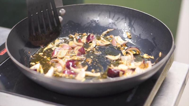 Oignon frit en huile dans une poêle clip Sauté végétarien Consommation saine Vue supérieure Légumes de sauté de vue supérieure de photos stock