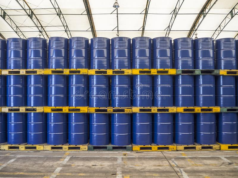 Oil barrels or chemical drums stacked up. Blue steel oil barrels or chemical drums stacked up in warehouse royalty free stock photos