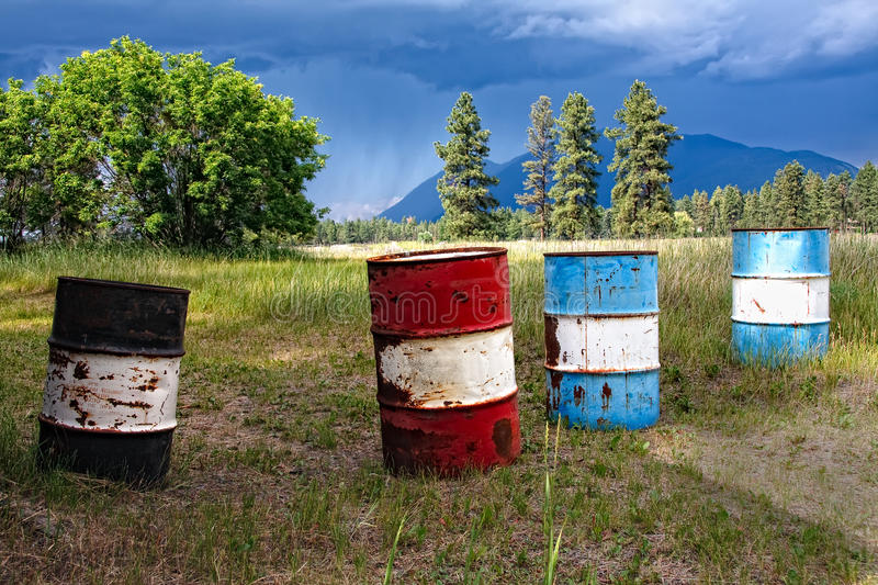 Oil Barrels Before A Storm. Oil barrels in a West Kootenay, BC, Canada field. Strong lighting before a storm passed through. Red and Blue oil drums against royalty free stock photography