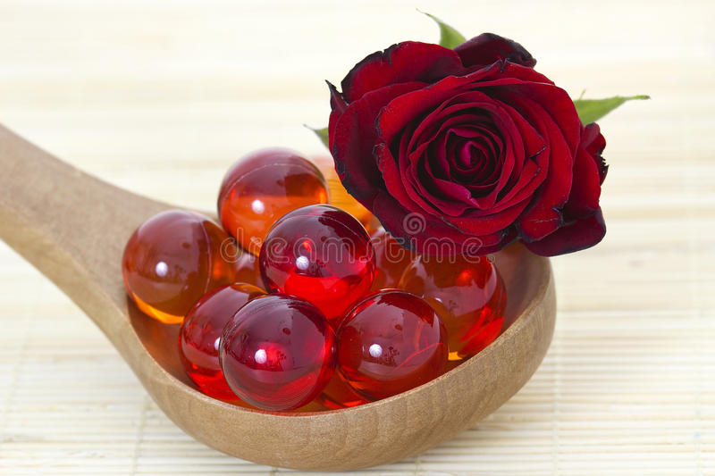Oil bath pearls and fresh rose stock photography