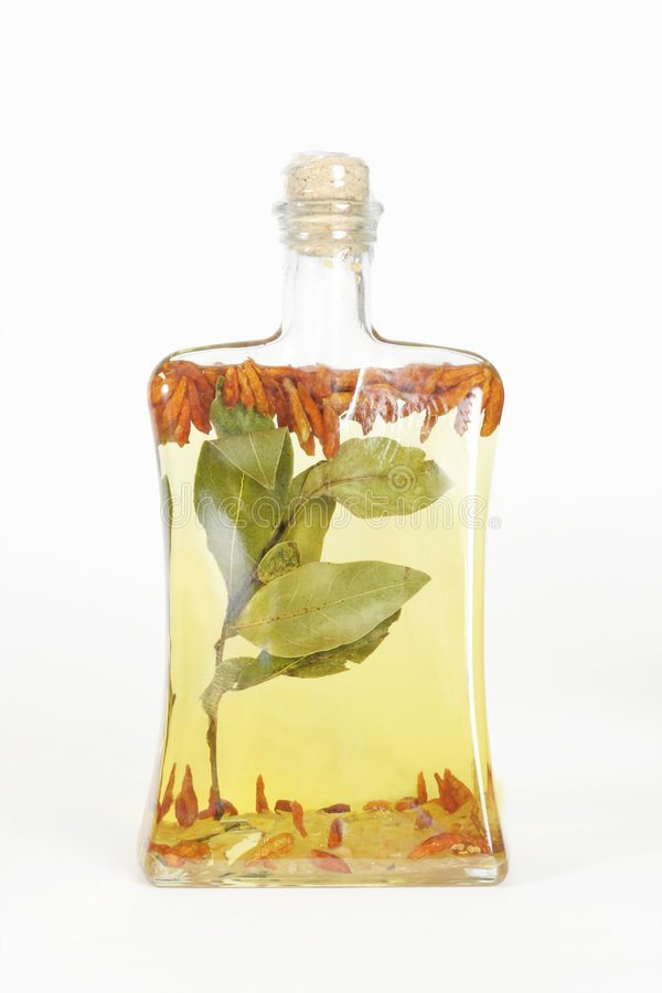 Oil bottle. A glass bottle filled with grapeseed oil, garlic, chilli peppers and bay leaves royalty free stock images
