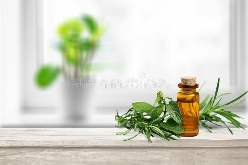 Oil bottle and green herbs on blue background. Green oil herbs bottle bottle green table background royalty free stock image
