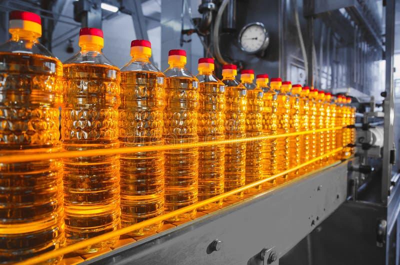 Oil in bottles. Industrial production of sunflower oil. Conveyor. Line for bottling and packing. Sunflower oil plant stock photos