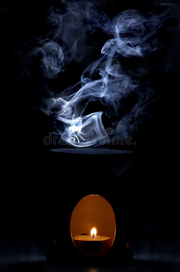 Oil burner. This simple oil burner has been shot in a dark room with simple black background, and the smoke has been backlit using a remotely controlled flash royalty free stock photo