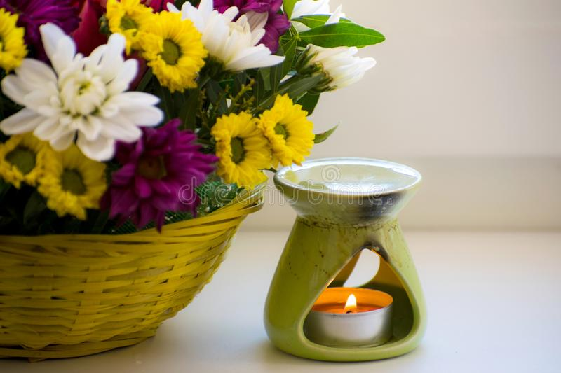 Oil burner with chrysanthemums by the side. Aromatherapy burner. Oil, aromatherapy burner, flowers and candles for spa and relaxat royalty free stock photos