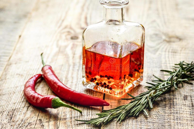 Oil in carafe with spices and chili on wooden background mock-up. Extra oil in carafe with spices and fresh chili on wooden desk background mock-up royalty free stock photo