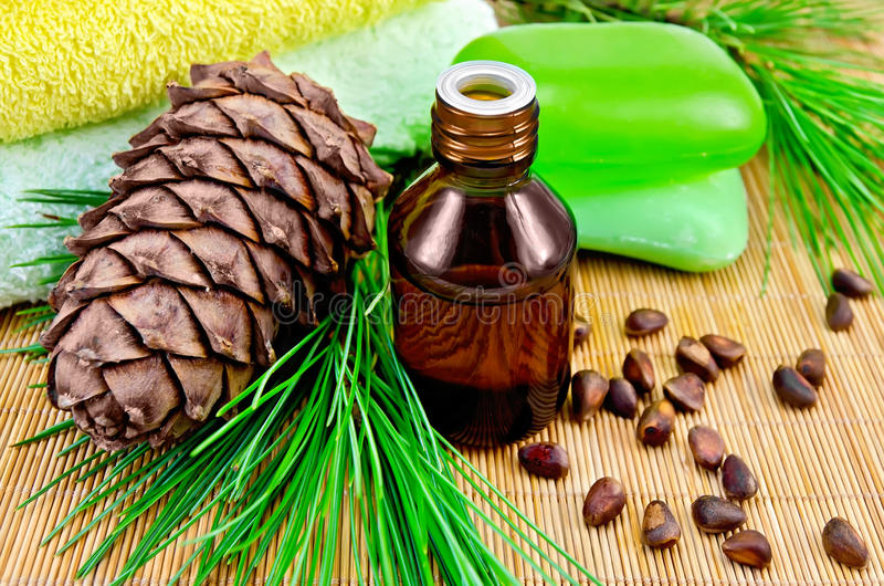 Oil cedar with pine cones and soap. Cedar oil in a bottle, with a branch of cedar cones, cedar nuts, two green soap, two towels on a bamboo mat stock images
