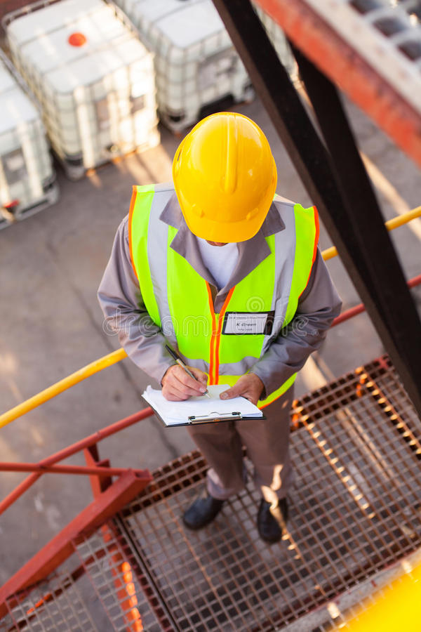 Oil chemical worker. Senior oil chemical worker working in refinery plant royalty free stock images