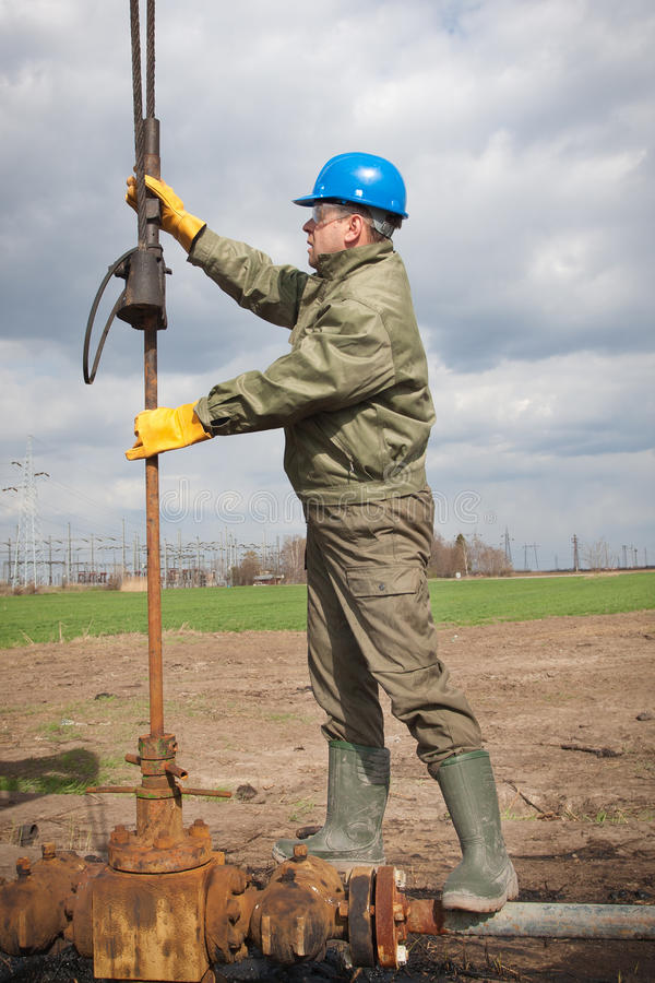 Oil company worker on the well. Oil company worker in a protective suit of wells royalty free stock photography