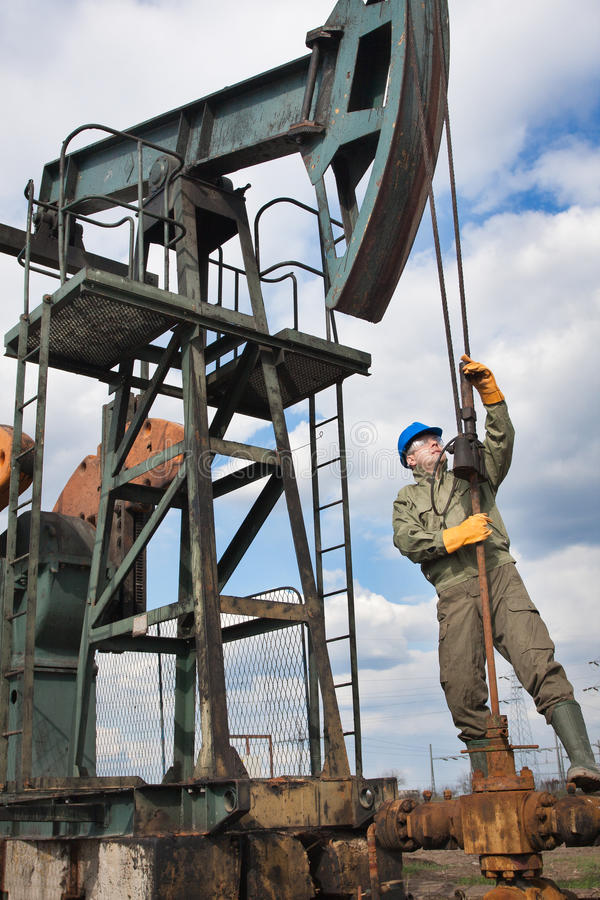 Oil company worker on the well. Oil company worker in a protective suit of wells stock image