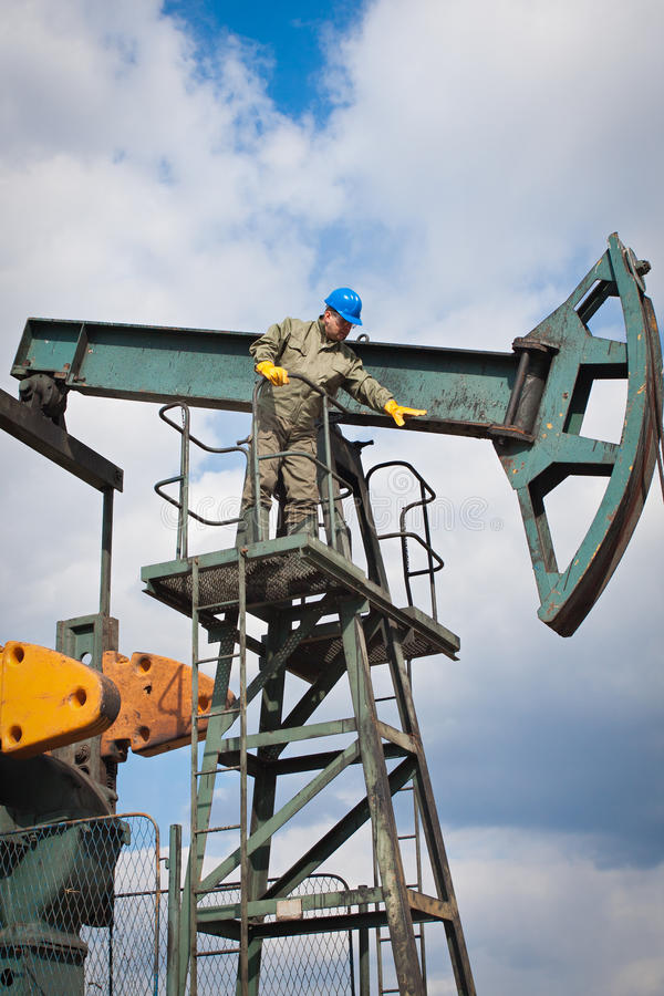 Oil company worker on the well. Oil company worker in a protective suit of wells stock images