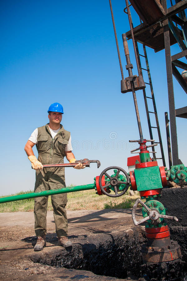 Oil company worker on the well. Oil company worker in a protective suit of wells stock photo