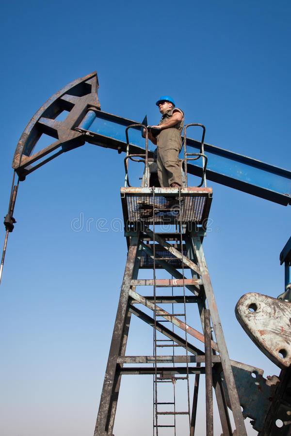 Oil company worker on the well. Oil company worker in a protective suit of wells stock photography
