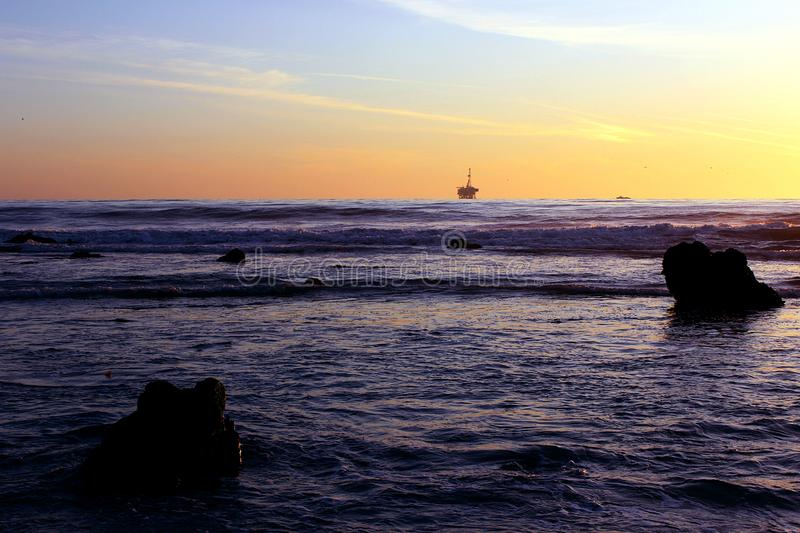 Oil Derrick and Rocks at Sunset in Goleta, California stock photo